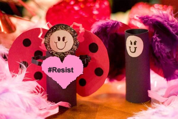 "Photo of arts-n-craft scene, hot pinks & purples, smiling winged tube figures, 1 w/ sign ""#Resist"""